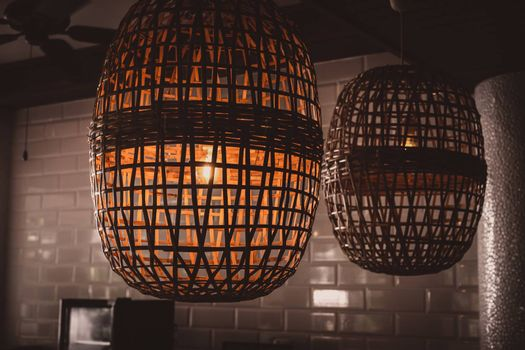 Vintage Style Design. Interior of hanging Lamp  illuminated, ceiling light lamp covered with weave. Wooden wicker chandelier lamp loft style.