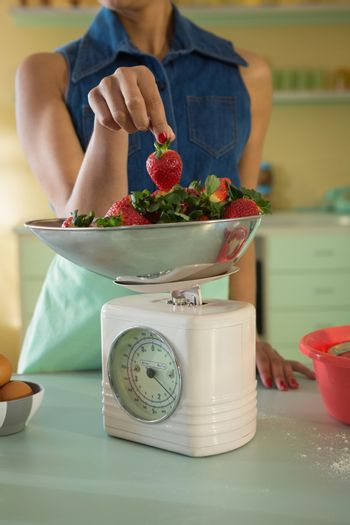 Young woman weighing strawberries on weighing machine in the kitchen