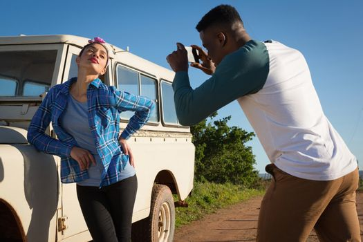 Man clicking picture of woman with mobile phone