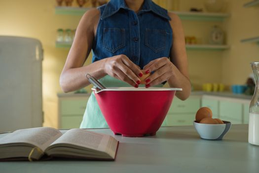 Young woman breaking an egg in to mixture bowl