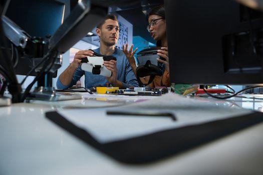 Computer engineers repairing motherboard at desk