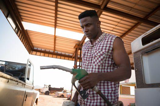 Man filling petrol in car at petrol pump