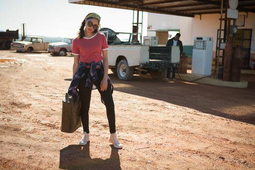 Woman holding a petrol can at petrol pump