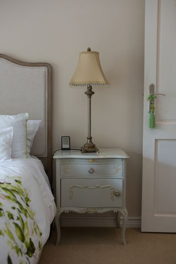Lamp on wooden bedside table in bedroom