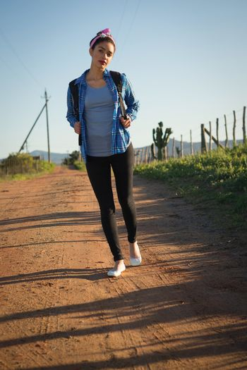 Woman walking on dirt track in countryside