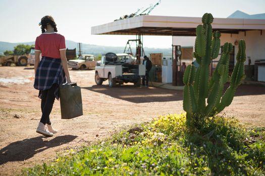 Woman walking with a petrol can at petrol pump