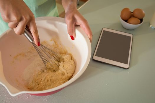 Young woman whisking mixture into bowl in the kitchen