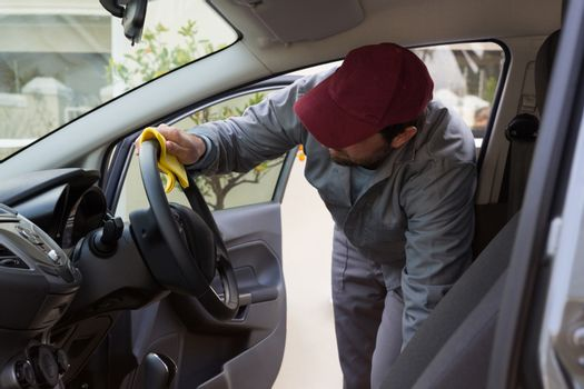 Auto service staff cleaning car interior