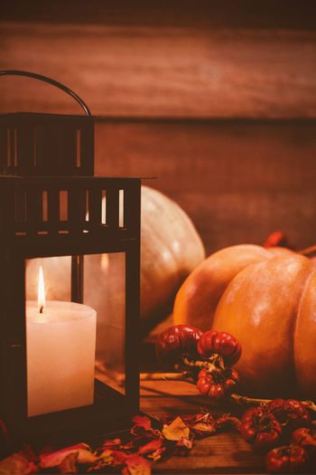 Pumpkins and burning candles on table during Halloween
