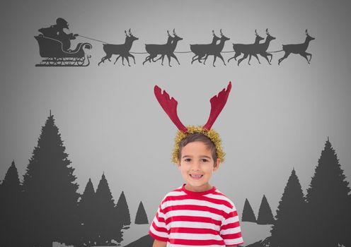 Boy against grey background with reindeer antlers on head and Santa flying in sleigh