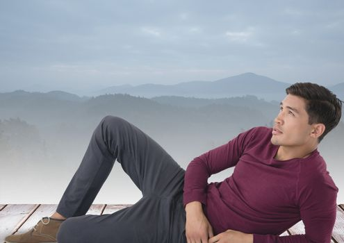 Man laying on platform over misty mountains