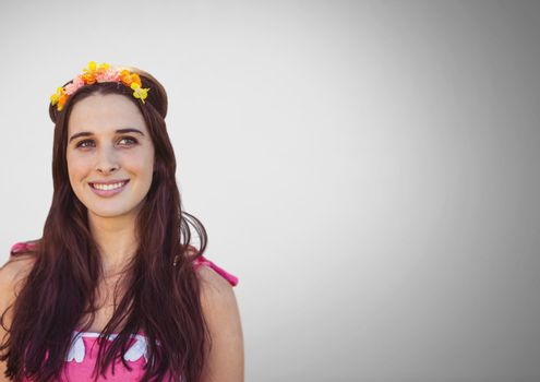 Young woman against grey background with flowers in hair