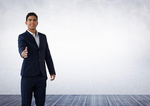 Businessman reaching for handshake in room