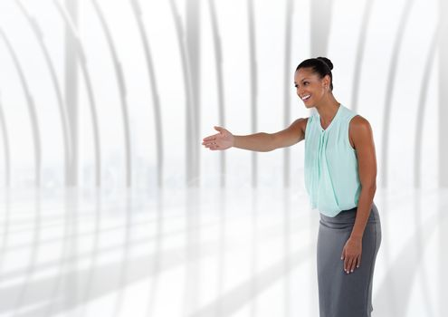Businesswoman  reaching out for handshake by windows
