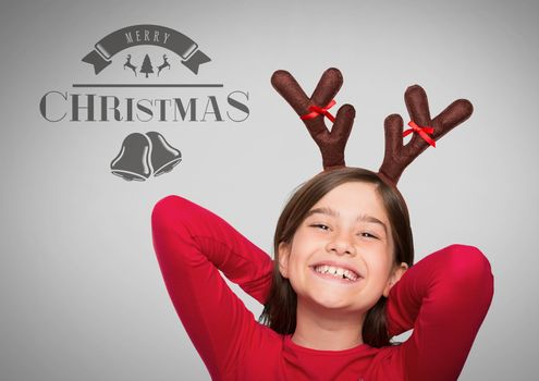 Girl against grey background with reindeer antlers and Merry Christmas text