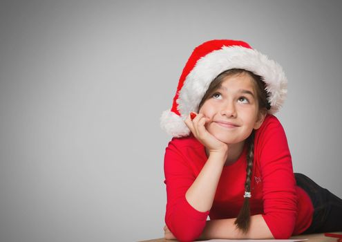 Girl against grey background with Santa Christmas hat and hair braid
