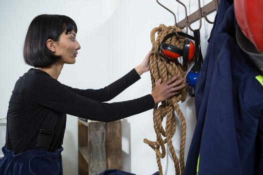 Female architect removing rope from hanger