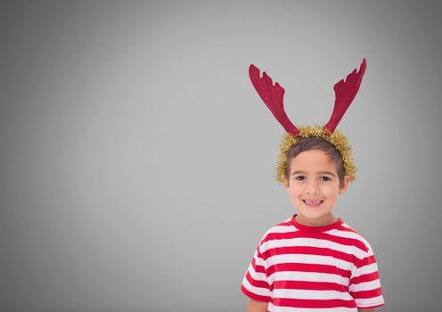 Boy against grey background with reindeer antlers on head