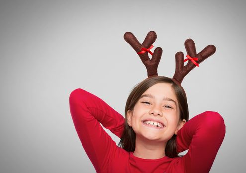 Girl against grey background with reindeer antlers