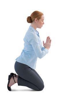 Businesswoman kneeling in prayer position