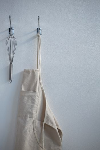 Apron and whisker hanging on hook