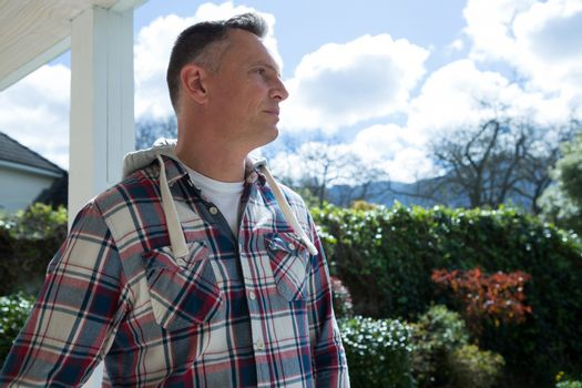 Thoughtful man standing in porch
