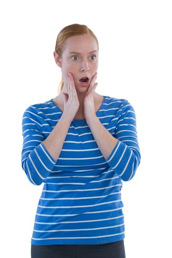 Woman with shocked facial expression standing with hand on face