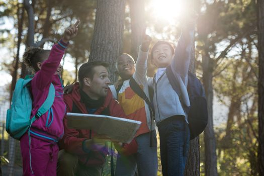 Kids pointing at distance in forest
