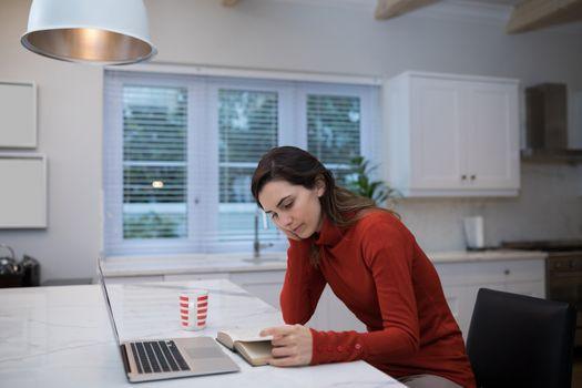 Woman reading novel at table