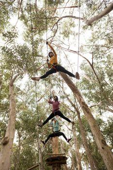 Friends on zipline in adventure park