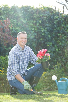Smiling man holding pot plant in garden