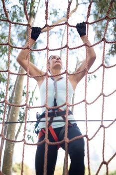 Determined woman climbing net