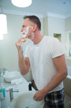 Man shaving his beard with razor