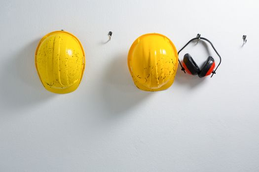 Hard hats and earmuffs hanging on hook