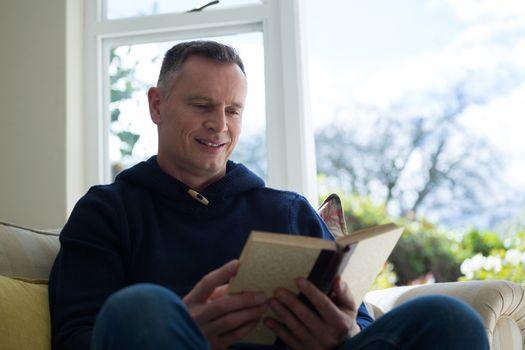 Man reading novel on sofa in living room