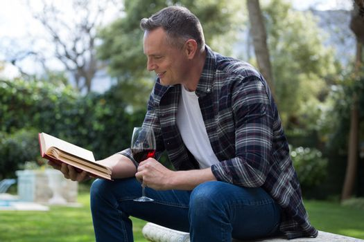 Man reading novel while having glass of red wine