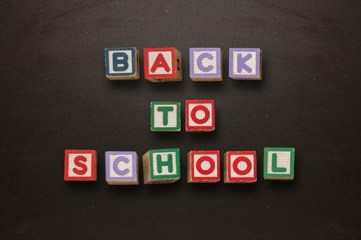Back to school message in blocks on blackboard