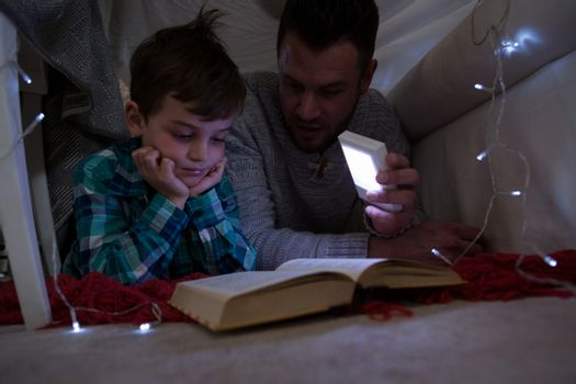 Father and son reading book under shelter