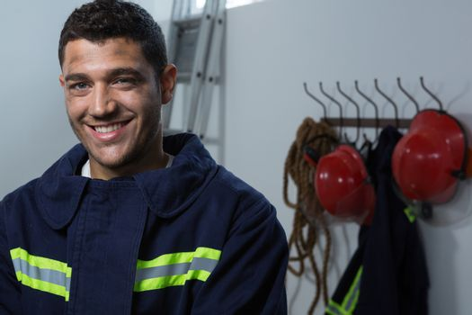 Smiling fireman standing in the office