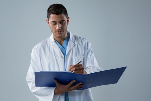 Doctor writing a reports in the file
