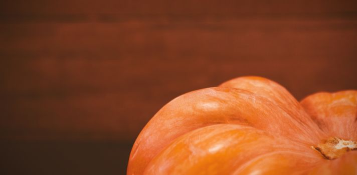Cropped image of pumpkin against wooden plank during Halloween