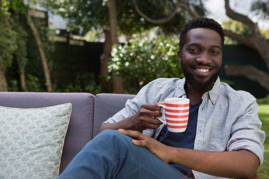 Happy man having black coffee in garden