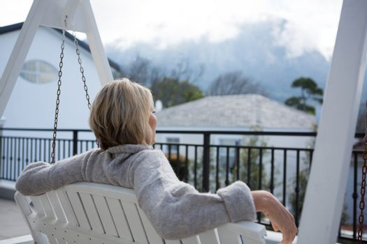 Thoughtful woman relaxing in porch