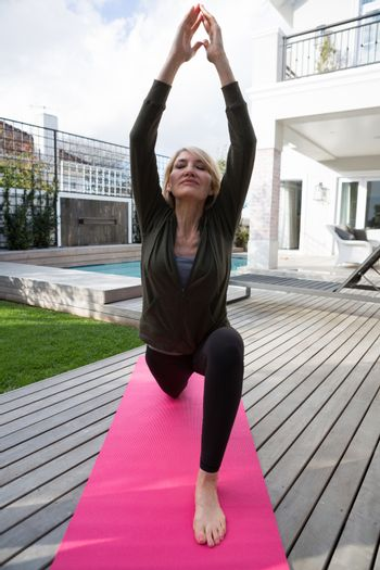 Woman practicing yoga in porch