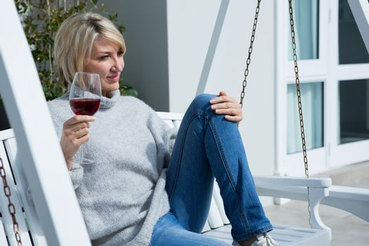 Thoughtful woman having wine in porch
