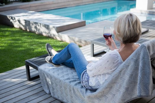 Woman having wine in porch