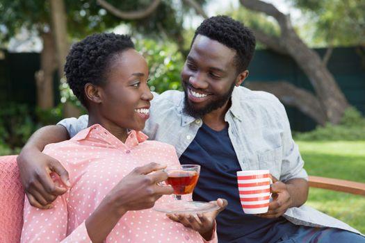 Happy couple having lemon tea and black coffee in garden