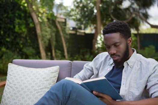 Man reading a novel in garden