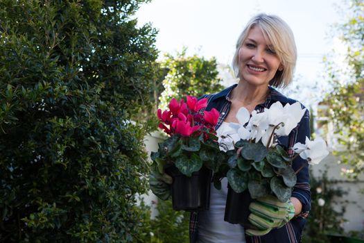 Portrait of woman holding pot plant in garden