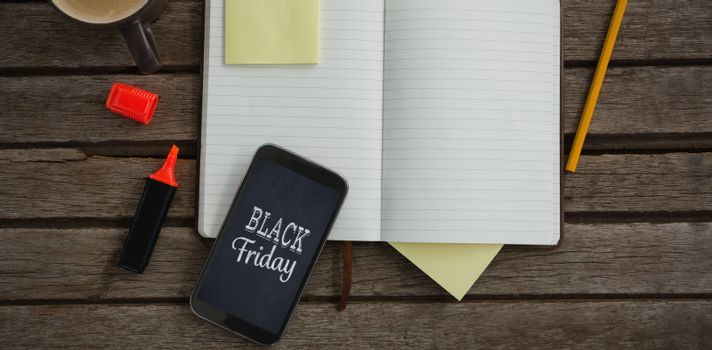 Organizer, coffee, mobile phone and stationery on wooden plank against black friday